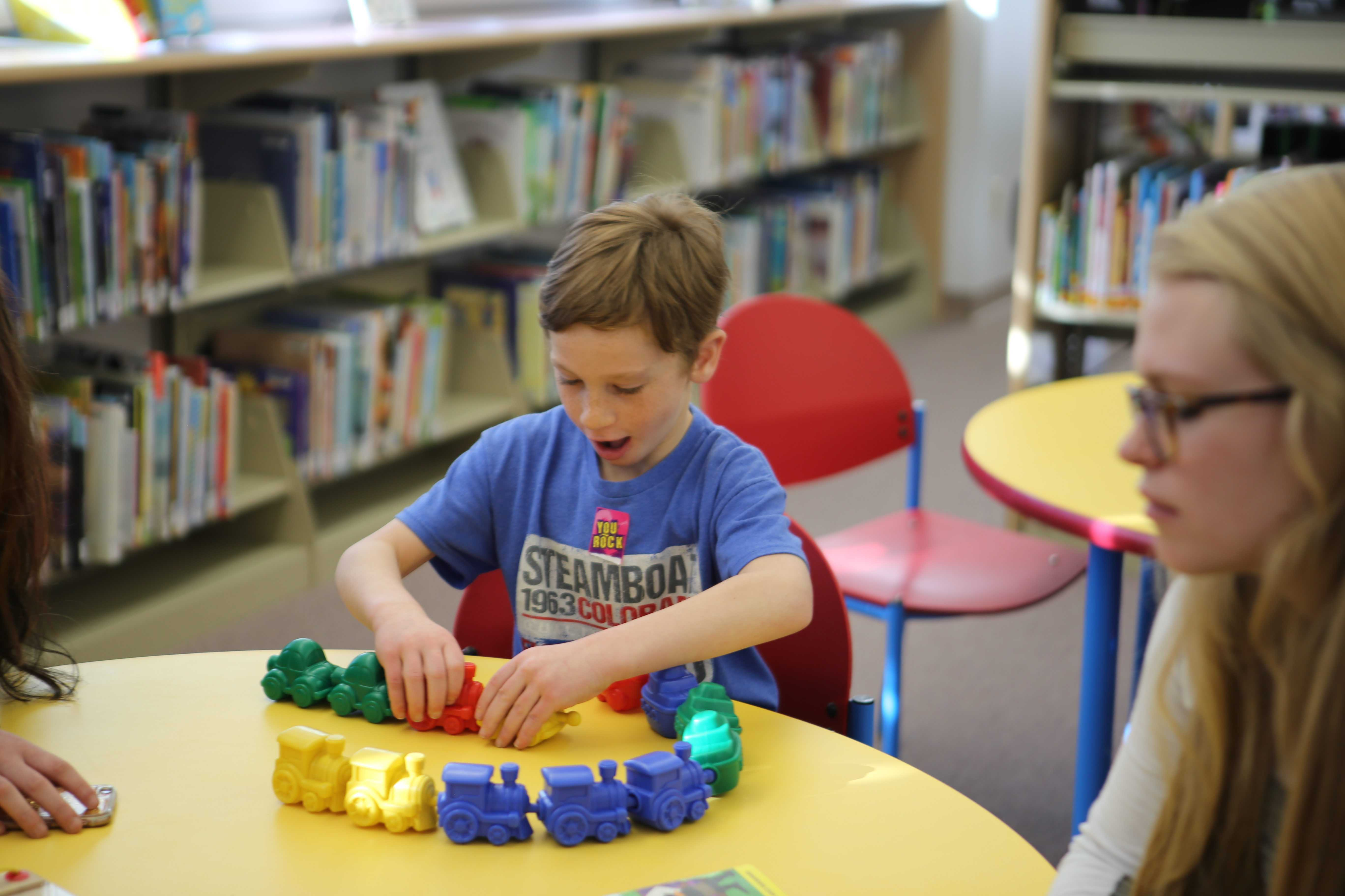 Luke Shepard's face lights with excitement as he plays with trains during Piaget play day on Thursday, March 2.
