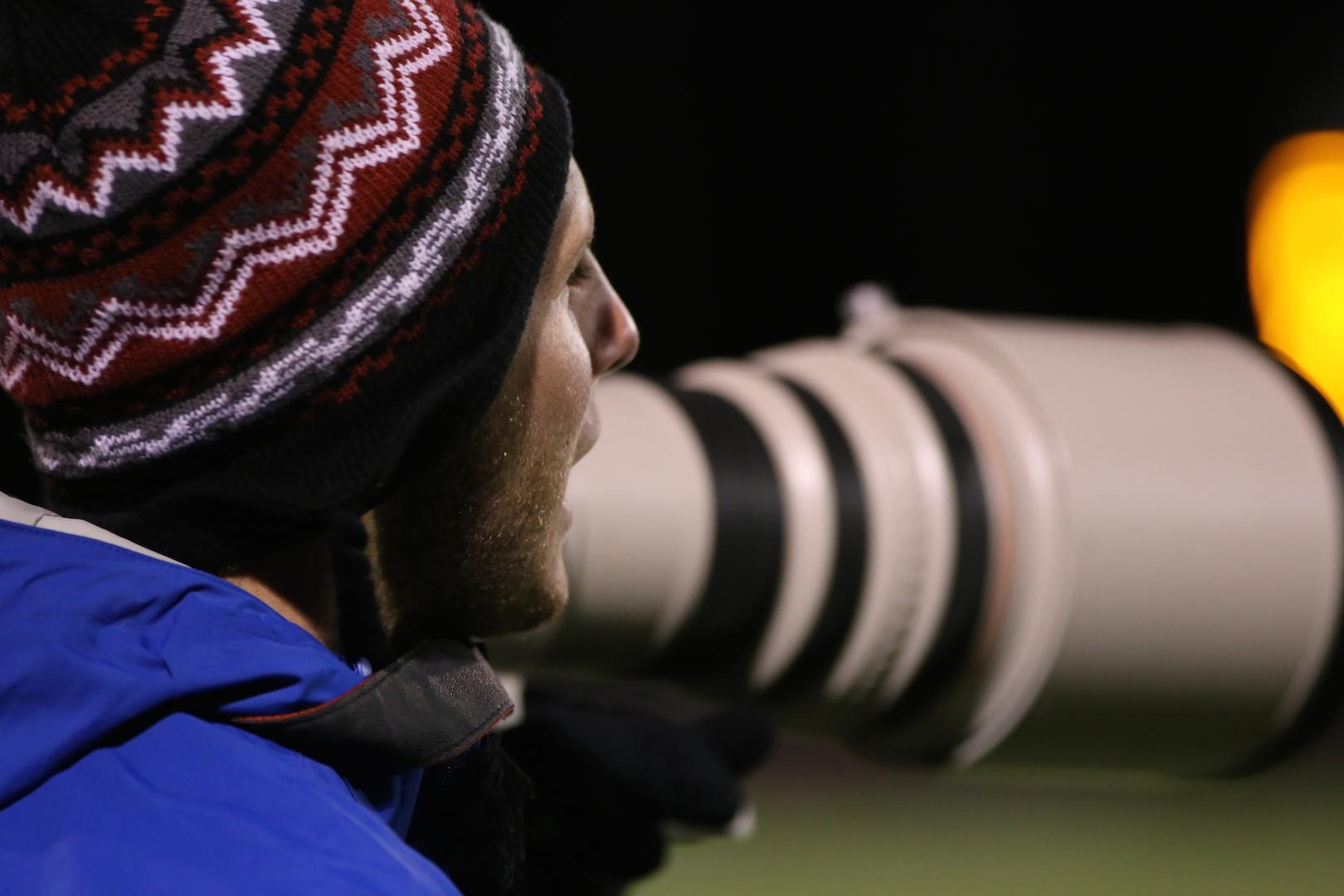 Meyer photographs a football game. He moved to the United States because his father's job was transferred.