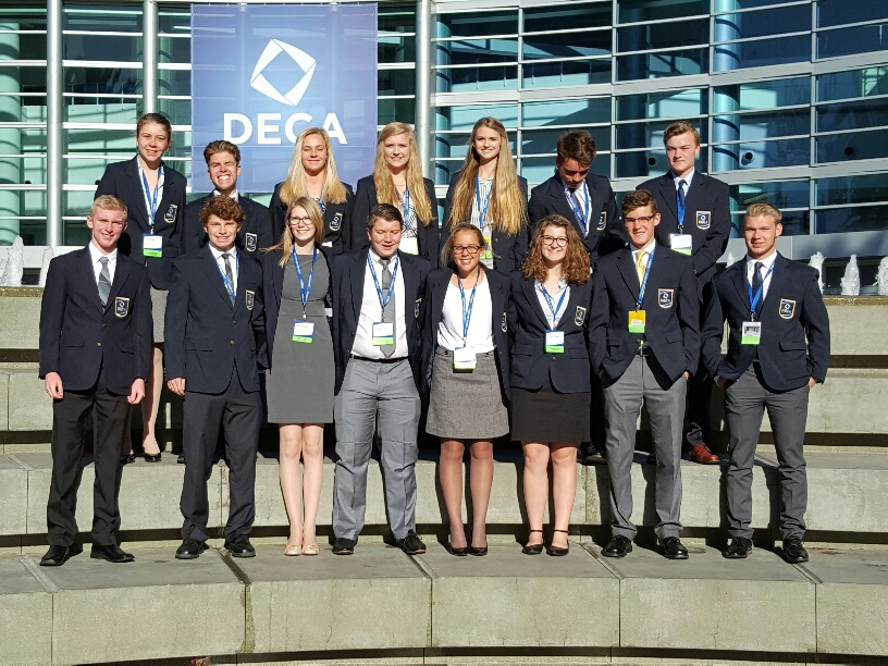 DECA+poses+in+front+of+their+logo.