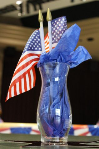 A vase holding mini American flags and blue tissue paper sits in the center of one of the cafeteria tables. Student government spent time putting up red, white, and blue decorations throughout the cafeteria, in honor of the upcoming holiday.   Photo courtesy of Katherine Ryan