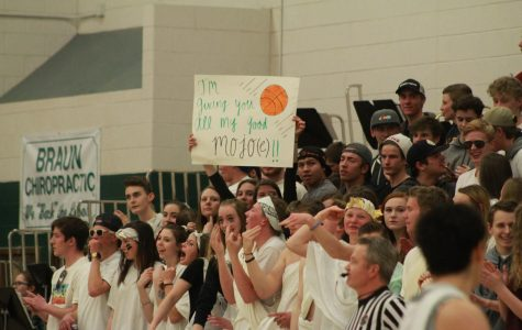 """Conifer students dressed in white cheer on the Lobos in the first playoffs game against Pueblo County. The night had a """"Greek"""" theme, so some students took the opportunity to dress up in togas and leafy, golden headbands. Some even came prepared with handmade signs."""