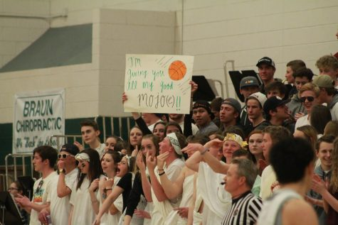 "Conifer students dressed in white cheer on the Lobos in the first playoffs game against Pueblo County. The night had a ""Greek"" theme, so some students took the opportunity to dress up in togas and leafy, golden headbands. Some even came prepared with handmade signs."