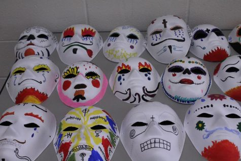 Day of the Dead masks line a table in a Spanish classroom.