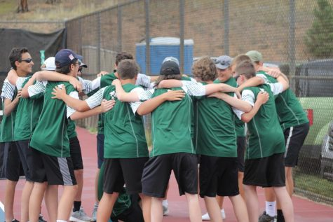Freshman Tim Starr (far left) joins in a pre-match ritual with the members of the tennis team.