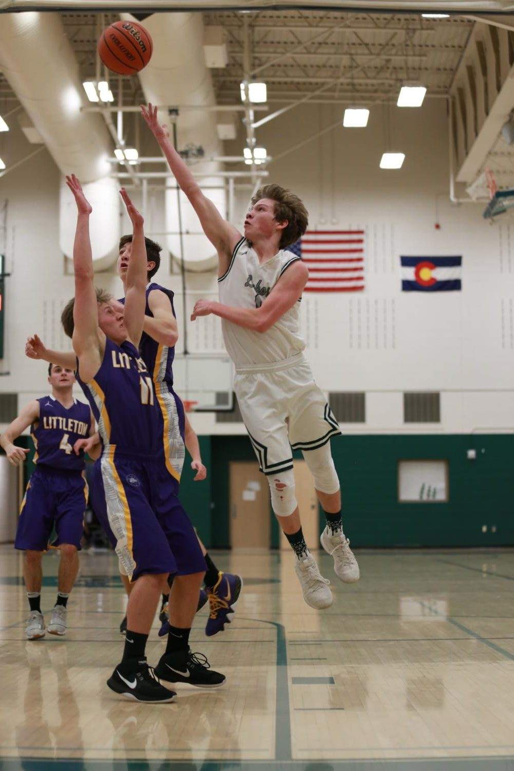 Junior Landon Wallace flies above a Littleton defender to score two of his six total points in the game on Tuesday, January 15.  The Lobos won, 58-55.