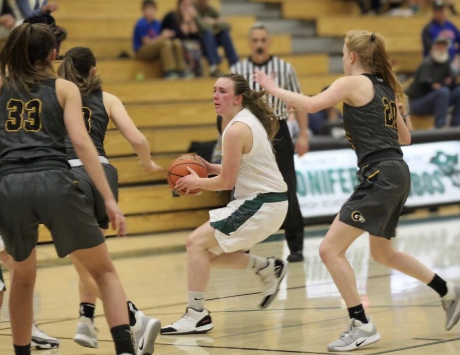 Senior Sierra Hayes taking the ball down the court surrounded by Green Mountain players