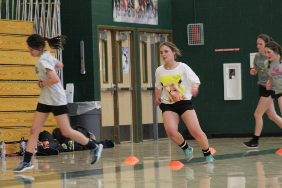 Freshman Julia Gnuechtel works on drills for soccer in the gym.