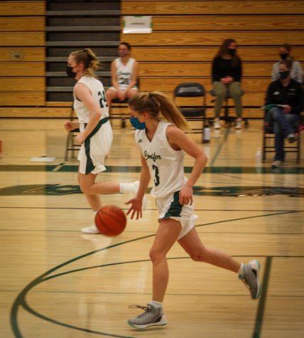 Junior Olivia Sinnett brings the ball down the court