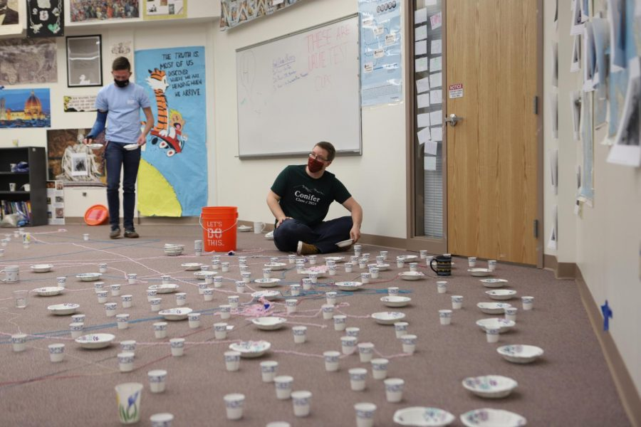 With only half an hour until class starts, Mr. Volzke works to empty the hundred plus dixie cups of water that were placed all over his room.