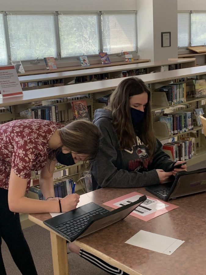 Cassidy Martin and Riley Hyatt, freshmen in Leslie Thompson's English class, use phones, Chromebooks, and QR codes to take part a