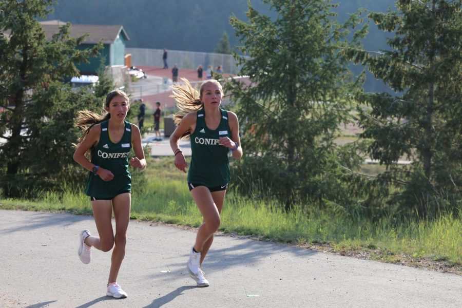 Sophmore Audrey VanWestrienen (left) and junior Joelle Wageman near the end of the first mile of the Conifer Climb course. I knew that Audrey was right behind me so I wanted to stick with her as best I could, Wageman said.