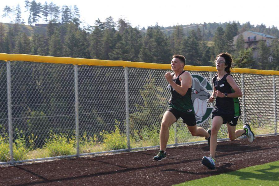 Freshman Nolan Schwemlein (right) races a DEvelyn runner to the finish of the Conifer Climb. Schwemleins final time was 23:41.