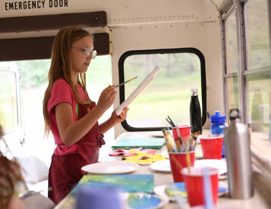 9 year old Skylar paints a canvas to accompany the clay flower she created in a previous session aboard the School Bus studio