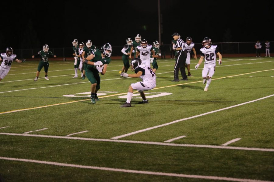 The Conifer High School football team taking the ball down the field.